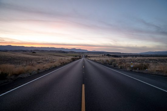 A shot of a highway road surrounded by dried grass fields under a sky during sunset